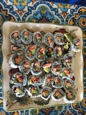 A plate of California roll with poached salmon and avocado