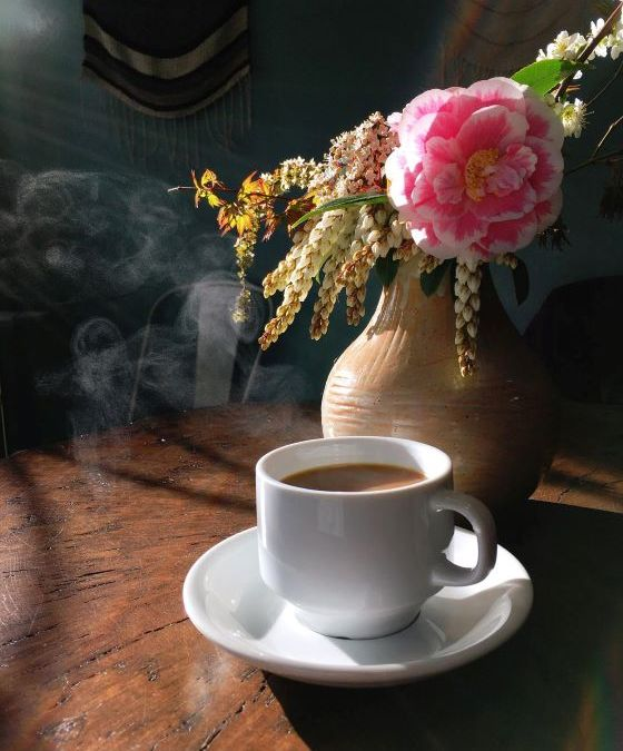 Cup of teaming coffee in front of a vase with pink flower