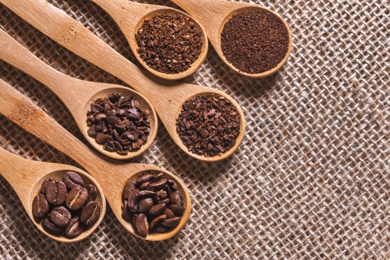 wooden spoon with different coffee grinds