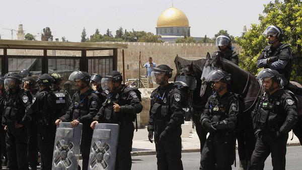 Israeli policemen stand guard before Palestinian men begin to pray in Ras al-Amud