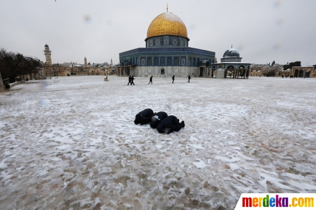Seorang warga melaksanakan salat di halaman Kubah Shakhrakh, kompleks Masjidil Aqsa, yang diselimuti salju, Jerusalem, Kamis (18/2/2021).