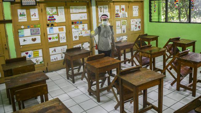 Petugas menyemprotkan disinfektan di ruang kelas SD Kenari 08 Pagi, Jakarta, Jumat (18/6/2021).  ANTARA FOTO/Galih Pradipta