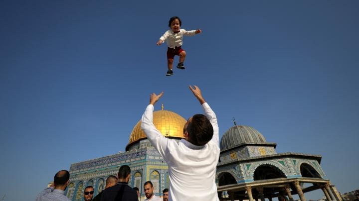Seorang warga Palestina bermain dengan anaknya saat merayakan Idul Adha di Kompleks Masjid Al Aqsa di Yerusalem, 20 Juli 2021. Warga Palestina bersuka cita merayakan Idul Adha dengan berkumpul di Masjid Al Aqsa. REUTERS/Ammar Awad