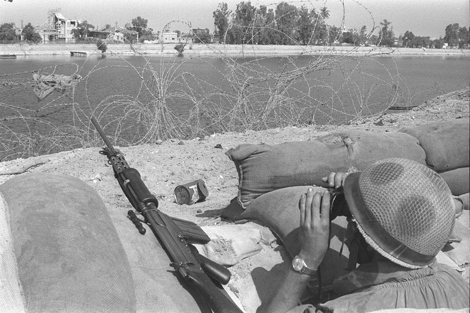 War of Attrition. Israeli soldier looking across th Suez Canal