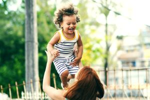 a woman holds a laughing child in her arms