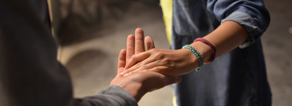 One person reaching out a helping hand to another person