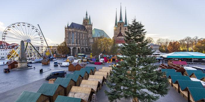 Auf einem großen Platz stehen eine Tanne, mehrere Häuschen und ein Riesenrad, im Hintergrund sind zwei Kirchen.