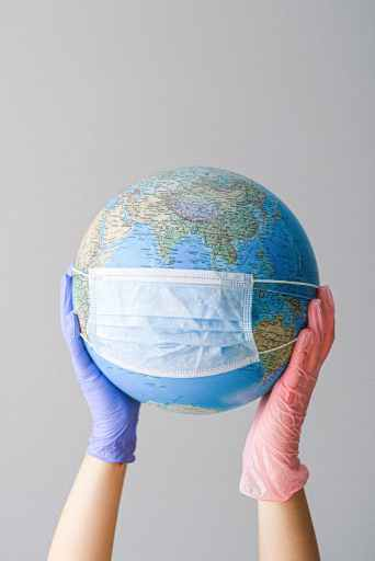 hands with latex gloves holding a globe with a face mask