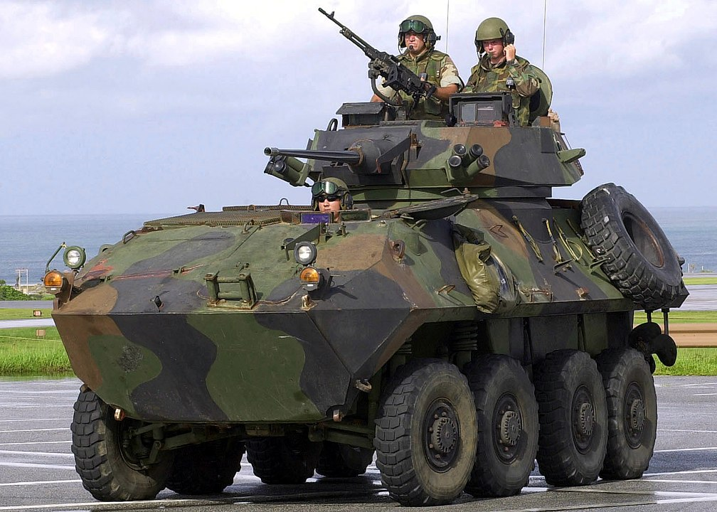 US Air Force (USAF) Security Forces Journeyman, Airman First Class (A1C) Robert Trusty, rides atop a US Marine Corps (USMC) Light Amphibious Vehicle (LAV-25) with USMC Corporal (CPL) Ronald Morrison, and driver Lance Corporal (LCPL) James Buttrey, while on patrol at Kadena AB, Japan. The LAV-25 is temporarily assigned to Kadena to provide security and is utilized to cross-train USMC and USAF Security Personnel during Operation ENDURING FREEDOM.