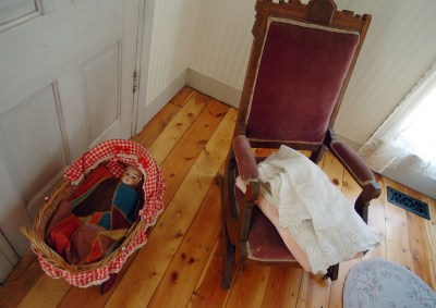 A doll bed and rocking chair in a bedroom of the Wise home.
