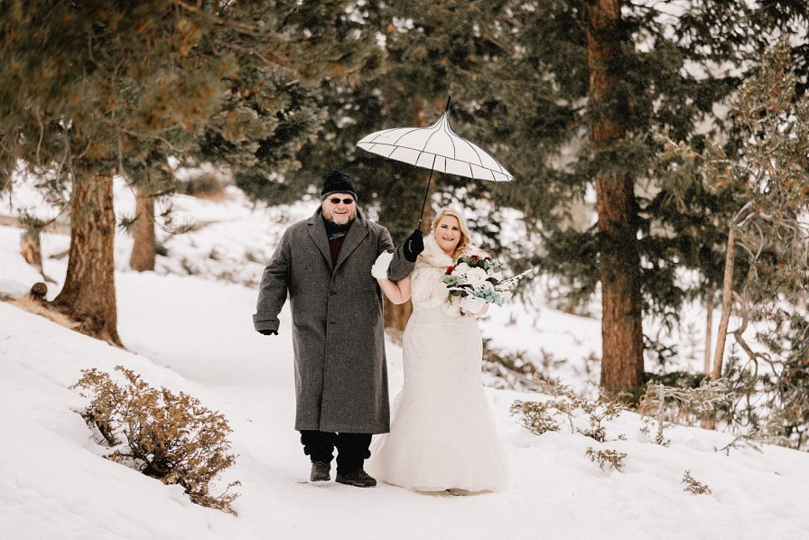 father walking bride down to snowy Sapphire Point elopement