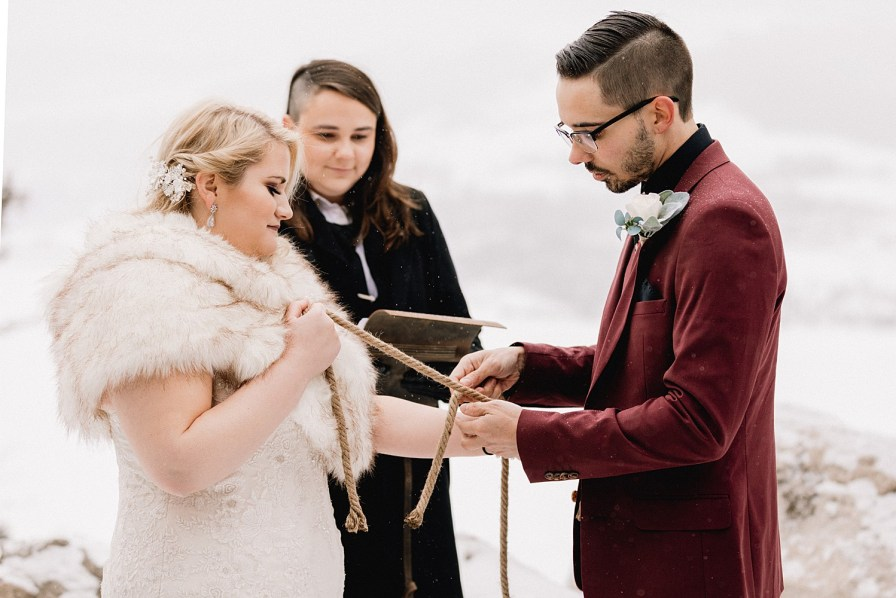 Couple ties rope knot in unity ceremony during their snowy Sapphire Point elopement