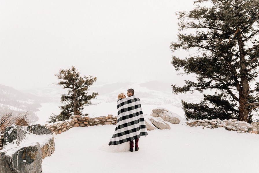 Couple wraps up in blanket after their snowy Sapphire Point elopement