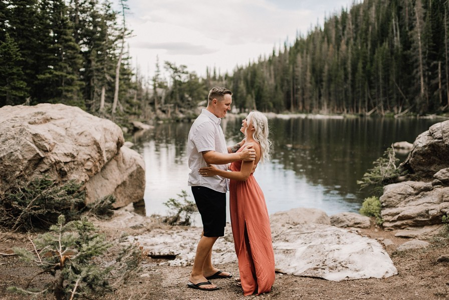 couple laughs together next to Dream Lake for their RMNP engagement