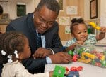 Alumnus Leon Denton with two young girls at a Salvation Army child care center