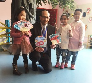 Children at an early childhood education site in China present gifts to Erikson President and Chief Executive Officer Geoffrey A. Nagle, Ph.D. Dr. Nagle and other leaders are in China to see firsthand the influence of an Erikson partnership that is training more than 1,000 early education professionals about best practices and theory.