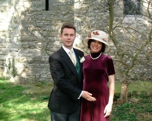 """The happy parents-to-be at a typical English wedding, with Katy admittedly """"thankful that my hat took a little of the focus off my belly."""""""