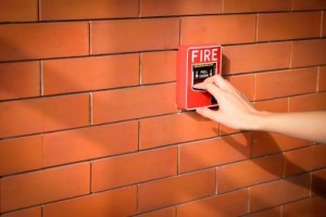 Hand Of Woman Is Pulling Fire Alarm On The Brick Wall