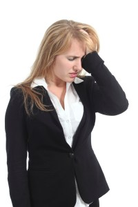 Stressed businesswoman with her hand in forehead and headaches migraines Boston denied claims lawyer