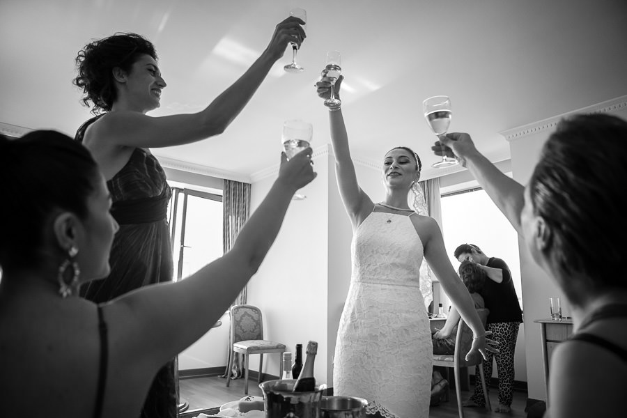 bride and friends raise a glass before wedding