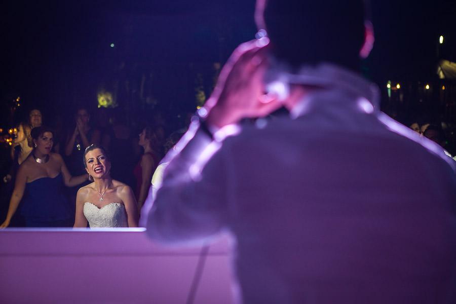 bride watching groom in dj cabin
