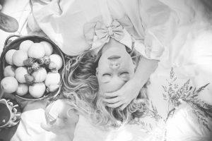 Julia liegt mit Hand im Haar auf der Picknickdecke, die Augen geschlossen