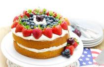 A sponge cake filled with whipped cream and topped with cream and fresh fruit