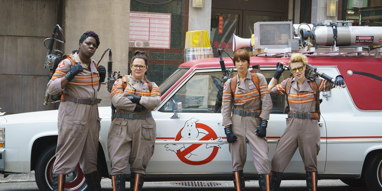 shot of ghostbusters standing in front of car in uniform