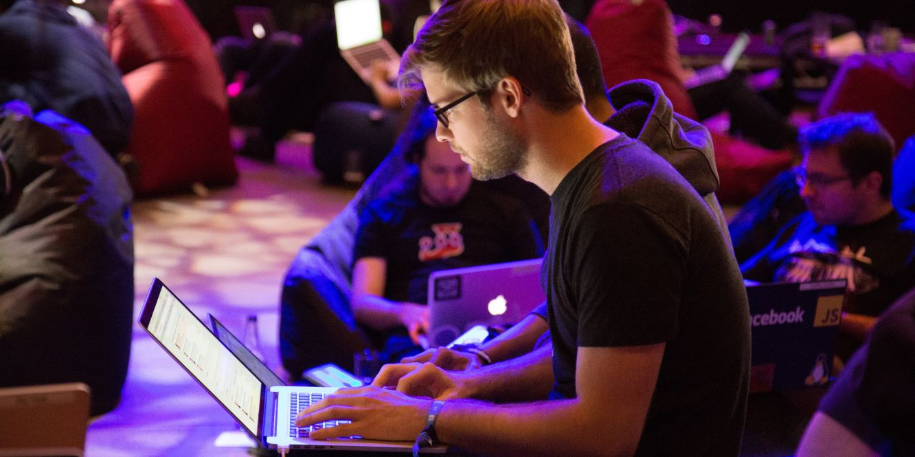 Photo of man on laptop in a large room filled with others also on laptops.