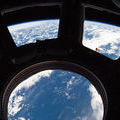 Earth and its horizon seen through the windows in the Cupola