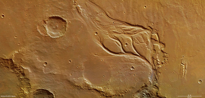 The central portion of Osuga Valles, which has a total length of 164 km. In some places, it is 20 km wide and plunges to a depth of 900 m. It is located approximately 170 km south of Eos Chaos, which is located at the periphery in the far eastern portion of the vast Valles Marineris canyon system.  Catastrophic flooding is thought to have created the heavily eroded Osuga Valles, which displays streamlined islands and a grooved floor carved by fast-flowing water. The water flowed in a northeasterly direction (towards the bottom right in this image) and eventually drained into another region of chaotic terrain, just seen at the bottom of the image.