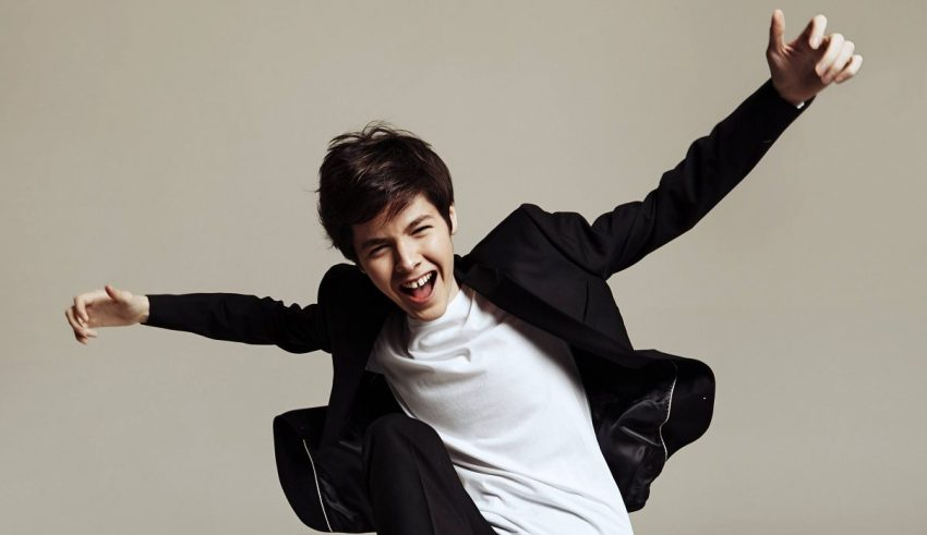 Kristian Kostov stands in front of a grey wall, posed with his arms stretched out wide.