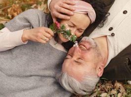 una pareja mayor acostada en el césped y riendo
