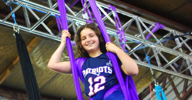 young girl smiling on an aerial fabric