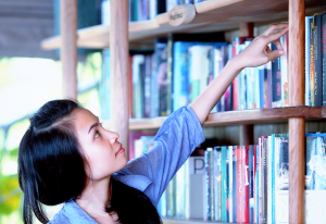 Young woman taking a book from a shelf