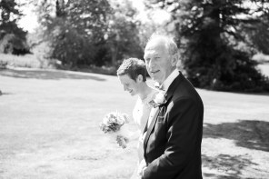 bride walking to ceremony in sunshine with father