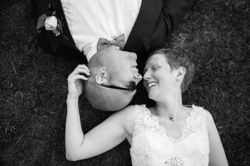 bride and groom lie on grass quirky relaxed wedding at ettington park
