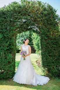 bride portrait garden archway bushes