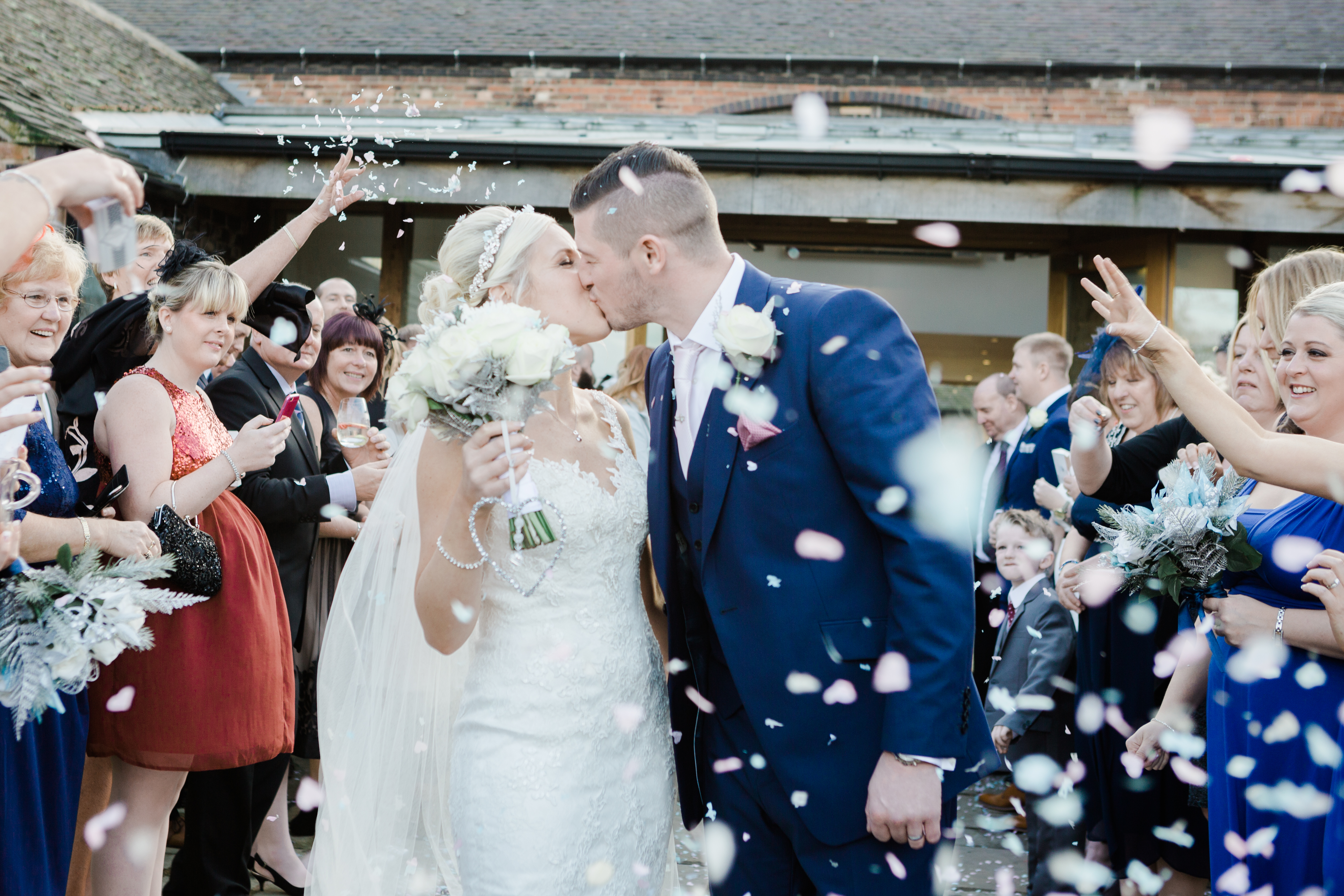 Bride and Groom kiss while confetti is thrown at Mythe Barn, silver and blue winter wedding