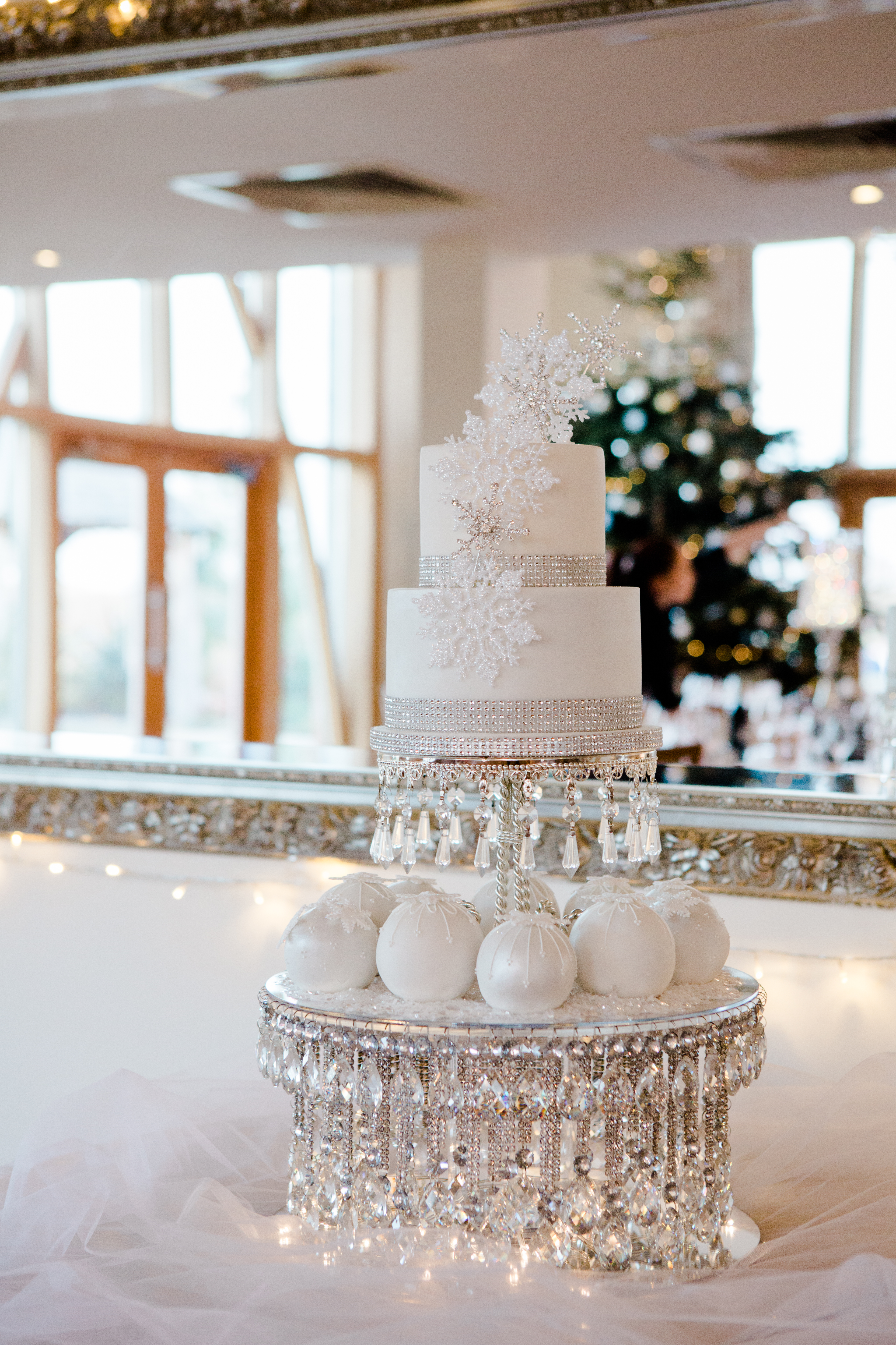 Winter wedding Mythe Barn cake white with snowflakes mini snowballs crystal cake stand with fairylights