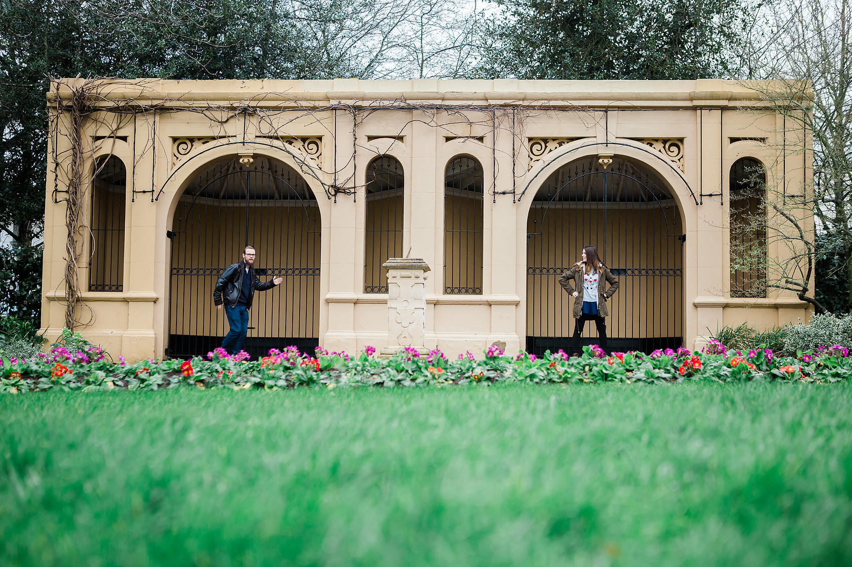 couple do funny quirky poses in front of monument in jephson gardens