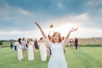 bride throws bouquet at sunset
