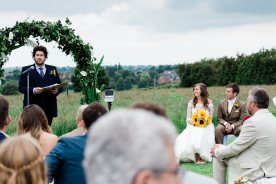 Bride and groom listen to brother reading out door ceremony