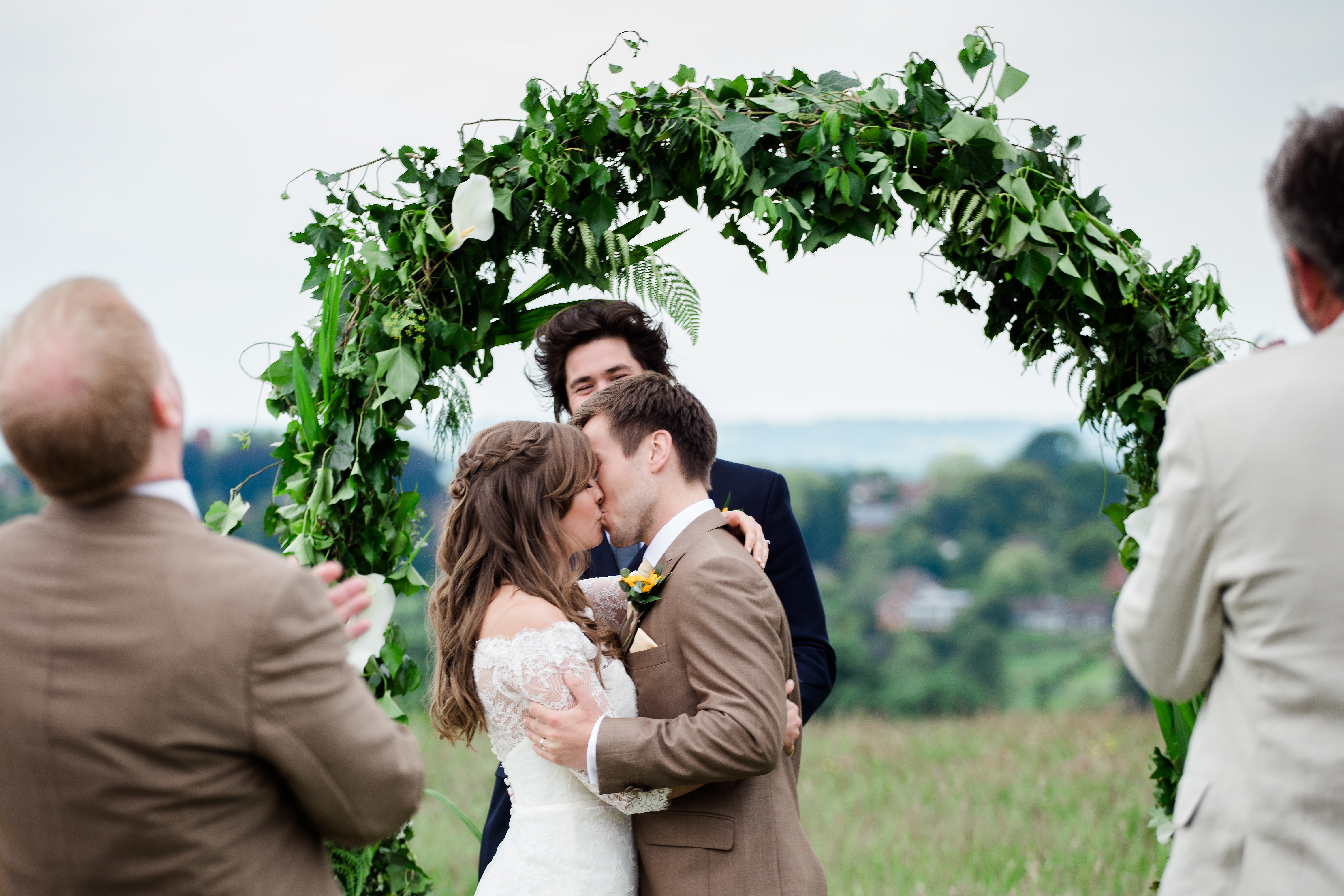 Couple kiss under flower arch outdoor ceremony