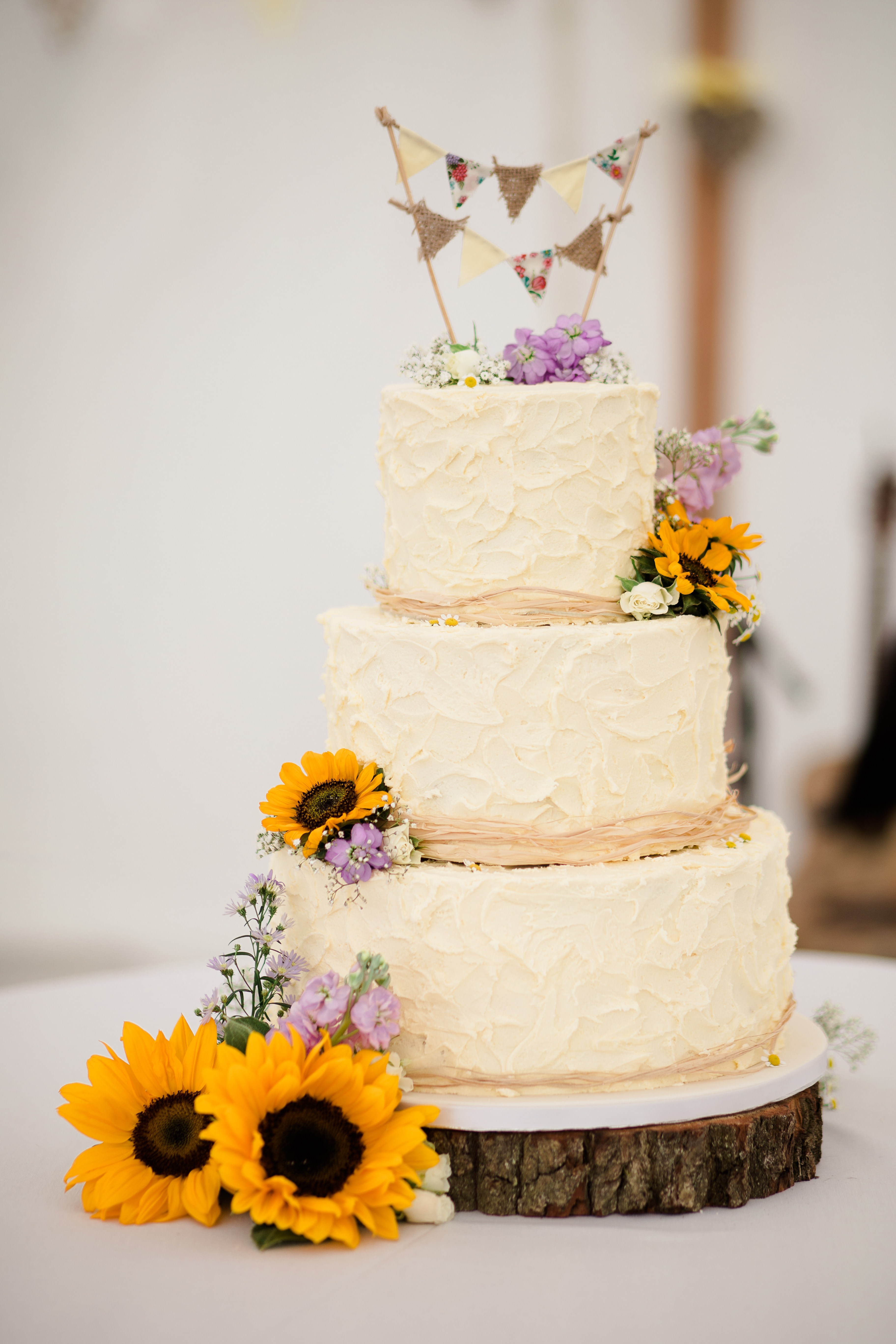 Cute rustic Textured icing wedding cake sunflower decoration and mini bunting