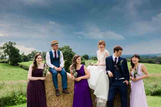 bridal party around haybales with moody skies