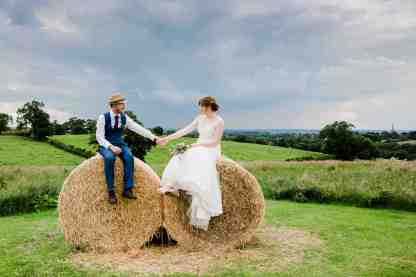 couple hold hands on hay bale home farm under moody skies daventry
