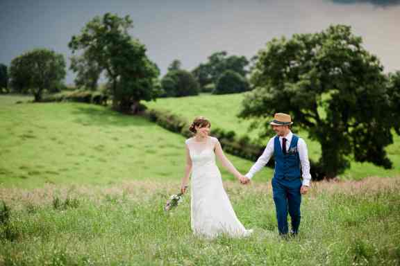 bride and groom smile while walking through grass at home farm