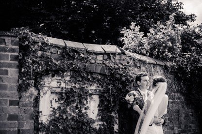 bride and groom by cute wall Bradley Church & Pendrell Hall wedding