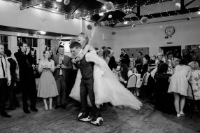 Bride being piggybacked around dancefloor on hoverboard